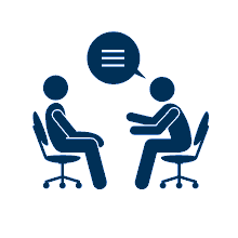 Two people sitting in chairs and talking.